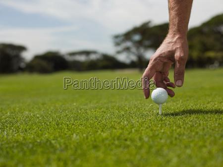 man playing golf picking up ball