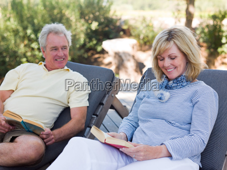 mature couple reading on loungers in