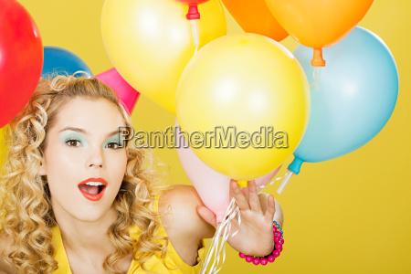 junge blonde frau mit luftballons vor