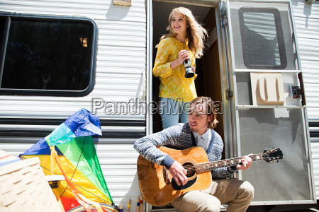 young couple by caravan with guitar
