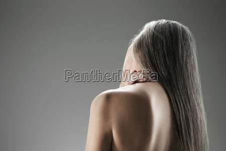 topless senior woman rear view