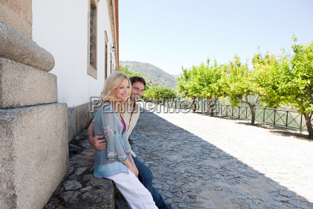 couple sitting by building