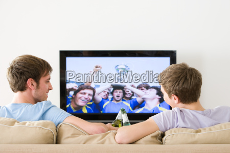 two young men watching football on