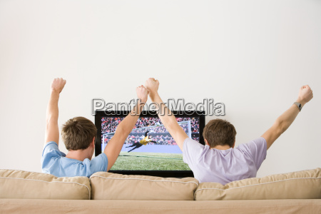 two young men cheering at football