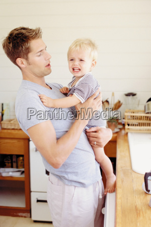 father and crying child in the