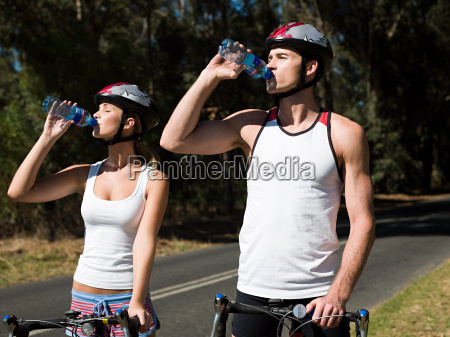 young couple cycling on road