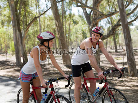 young couple cycling in forest