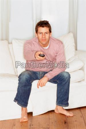 grumpy young man watching tv