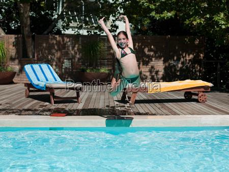 girl jumping into swimming pool