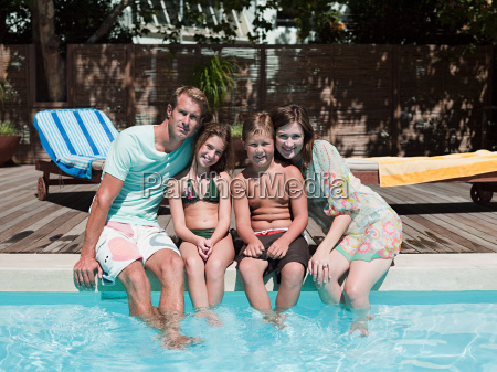 family sitting on edge of swimming