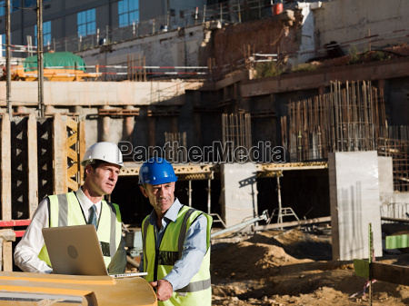 mature men using laptop on construction