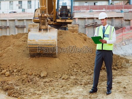 mature man with clipboard on construction