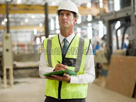 mature man with clipboard in factory