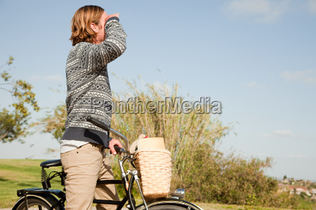 young man with a bicycle looking
