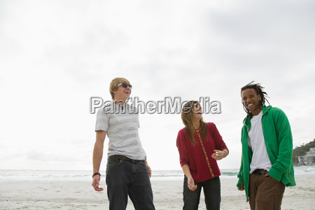 three young people on beach