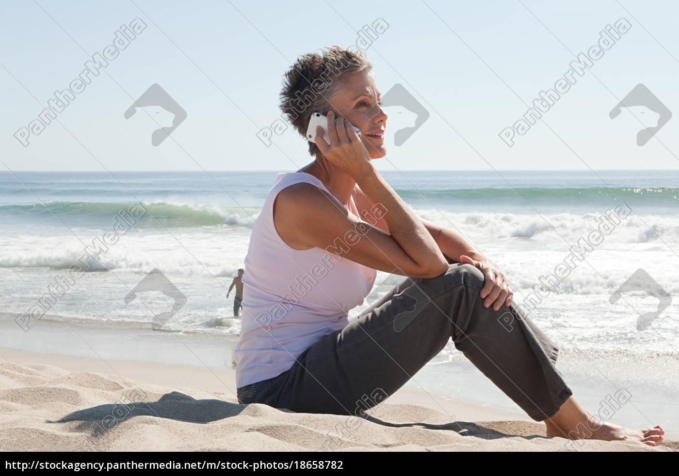 seniorin, mit, handy, am, strand - 18658782