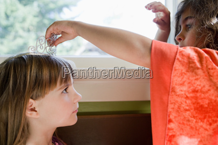 one girl putting tiara on another