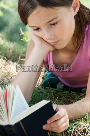 girls lying on front reading book