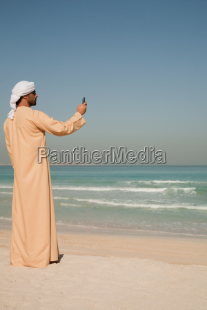 middle eastern man using mobile phone