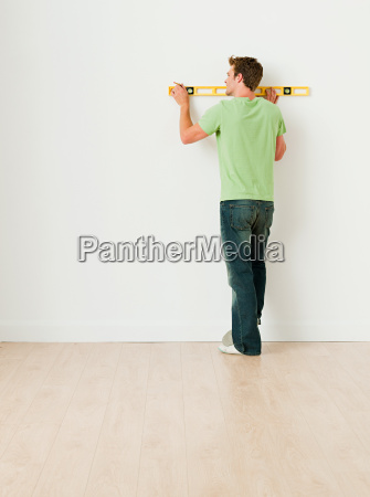 young man using spirit level on