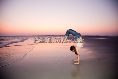 woman doing a handstand on beach