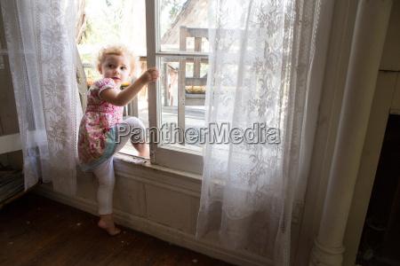 child climbing over opened window