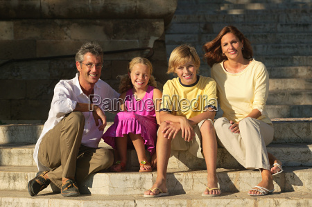 two generation family sitting on steps