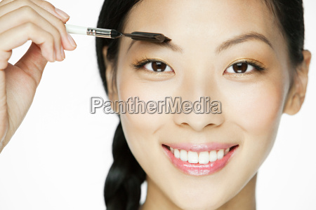 young woman using eyebrow comb