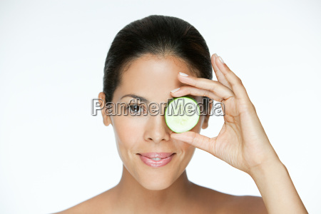 woman holding cucumber over eye