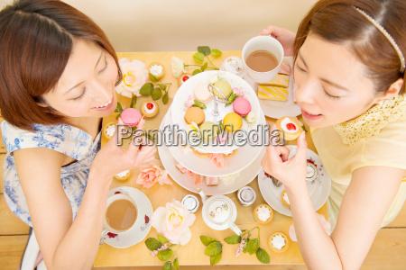 two happy women indulging in sweet