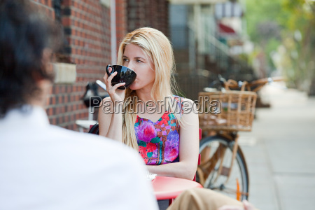 woman drinking coffee outside cafe