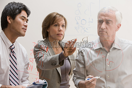 people looking at diagram on glass