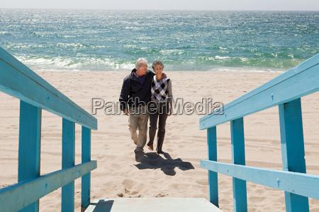couple walking on beach towards walkway