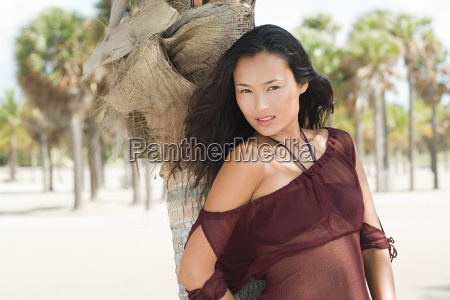 young woman by palm tree