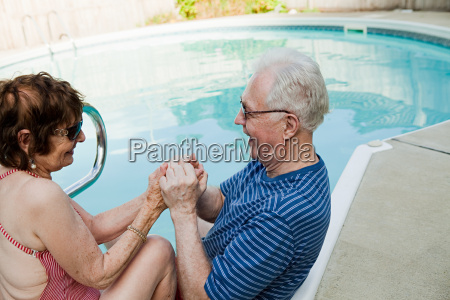 senior couple holding hands by swimming