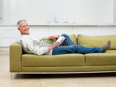 senior man sitting on sofa reading