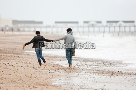 couple running hand in hand by