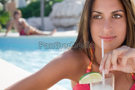 woman with drink by pool
