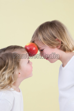 boy and girl with apple between