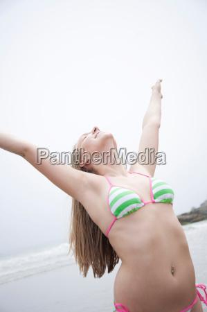 young woman in bikini stretching on