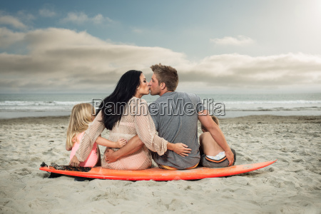 young family sitting on surfboard on