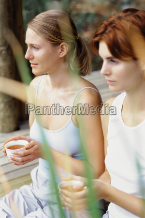 two women holding teacups