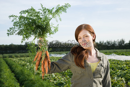 young woman holding bunch of carrots