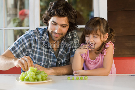 father and daughter with grapes