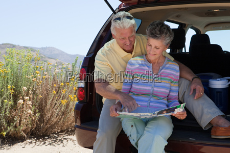 mature couple sitting on boot of