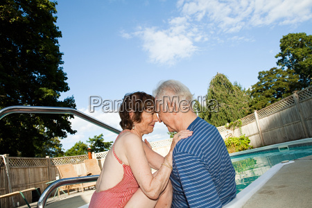 loving senior couple by swimming pool