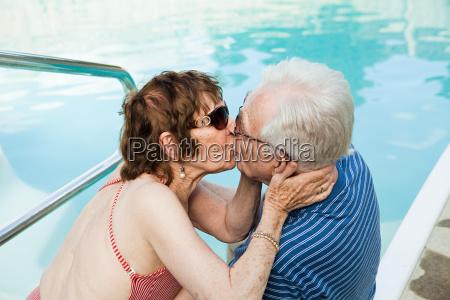 senior couple kissing by swimming pool