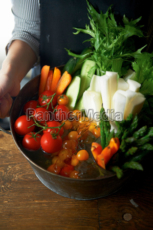 woman holding bowl of vegetables and