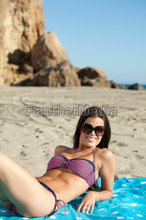 young woman sunbathing at the beach