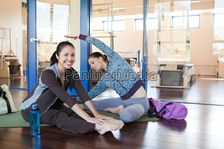 two women in gym one stretching
